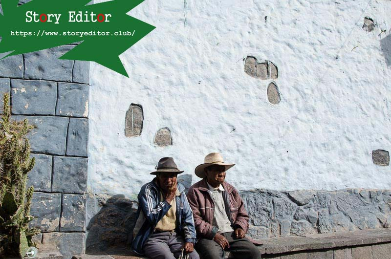 two men with wide-brimmed hats sitting on a stone bench against a whitewashed wall in a colca canyon town
