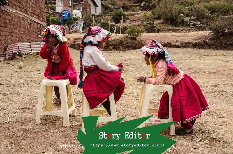 three little girls in colorful wool hats and red skirts with flight on four plastic stools lined up on the shores of lake titicaca one of the wonderful places in peru
