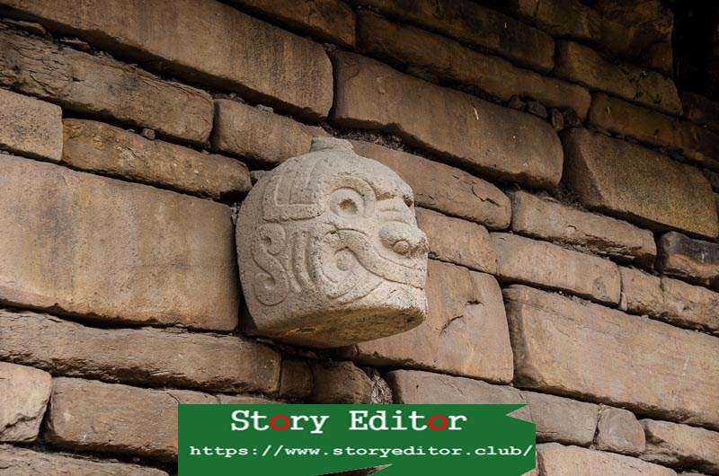 stone head in the shape of a jaguar with eyes and fangs engraved on a stone wall of chavín de huántar